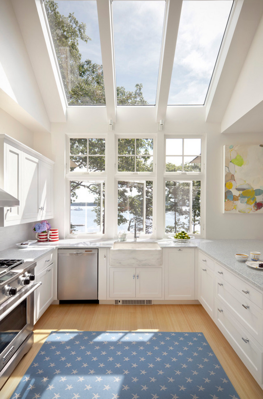 well lit kitchen with windows and skylight