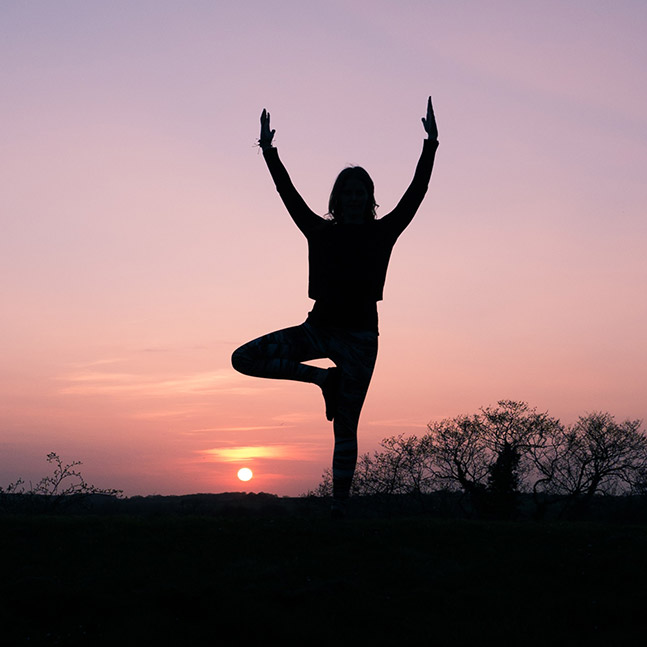 A silhouette of person practicing the tree yoga pose during sunset